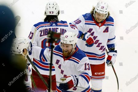 New York Rangers left wings Alexis Lafrenière (13), Artemi Panarin (10) and center Mika Zibanejad, left, celebrate leaving the ice after defeating the New Jersey Devils 3-0 in an NHL hockey game, in Newark, N.J