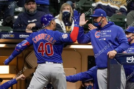 Chicago Cubs' Willson Contreras celebrates with manager David Ross after hitting a two-run home run during the eighth inning of a baseball game against the Milwaukee Brewers, in Milwaukee