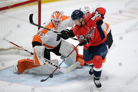 Philadelphia Flyers goaltender Brian Elliott (37) tracks the puck as Washington Capitals right wing Garnet Hathaway (21) tries for a shot during the first period of an NHL hockey game, in Washington