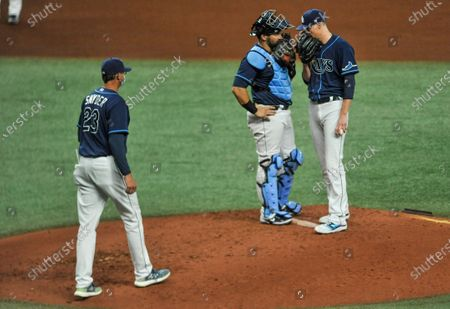 Tampa Bay Rays pitching coach Kyle Snyder (23) walks to the mound to talk with catcher Mike Zunino, center, and starter Ryan Yarbrough after loading the bases during the fourth inning of a baseball game against the Texas Rangers, in St. Petersburg, Fla