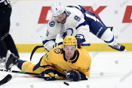 Tampa Bay Lightning center Tyler Johnson (9) falls onto Nashville Predators left wing Erik Haula (56) as they chased the puck during the first period of an NHL hockey game, in Nashville, Tenn
