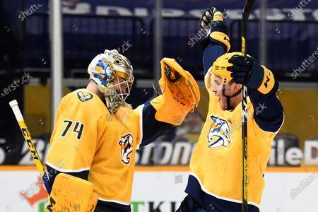 Nashville Predators goaltender Juuse Saros (74) celebrates with defenseman Jeremy Davies (38) after the Predators defeated the Tampa Bay Lightning in an NHL hockey game, in Nashville, Tenn