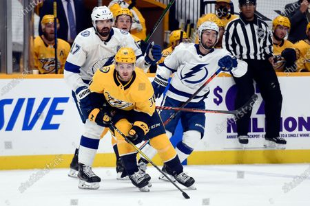 Stock Picture of Nashville Predators defenseman Jeremy Davies (38) plays against Tampa Bay Lightning left wing Alex Killorn (17) and right wing Mathieu Joseph (7) during the first period of an NHL hockey game, in Nashville, Tenn