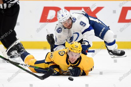 Tampa Bay Lightning center Tyler Johnson (9) falls on Nashville Predators left wing Erik Haula (56) as they chase the puck during the first period of an NHL hockey game, in Nashville, Tenn