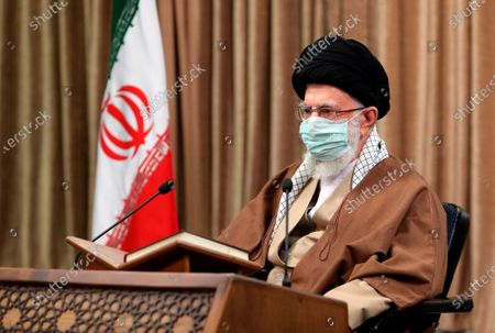 """In this picture released by an official website of the office of the Iranian supreme leader, Supreme Leader Ayatollah Ali Khamenei wearing a protective face mask, attends a meeting in Tehran, Iran, . Khamenei said Wednesday that the offers being made at the Vienna talks over his country's tattered nuclear deal """"are not worth looking at"""