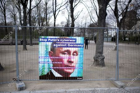 Deutschland, Germany, Berlin, 13.04.2021 Protest banner with photo of Wladimir Putin, president of Russia, Stop Putin's cyberwar against Germany, in support for Russian opposition member Alexei Navalny during a rally in front of the Brandenburg Gate in Berlin, Germany. The UnKremlin and the young Russian group Perestroj_card have set up a tent camp. With the action activists protest against Kremlin head Putin.