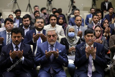 Abdullah Abdullah, Chairman of the High Council for National Reconciliation, center, prays before a press conference in Kabul, Afghanistan