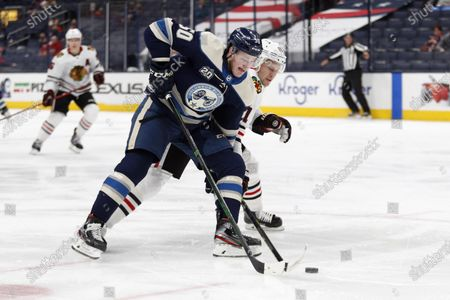 Columbus Blue Jackets forward Eric Robinson, left, reaches for the puck in front of Chicago Blackhawks defenseman Riley Stillman during an NHL hockey game in Columbus, Ohio, . The Blackhawks won 4-3 in overtime