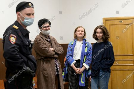 Stock Image of Magazine editors from left, Armen Aramyan, Natalya Tyshkevich and Alla Gutnikova wait for a court session as a police officer, left, stands next in Moscow, Russia, . Russian authorities levied criminal charges Wednesday against four young editors of an online student magazine that had coverage about the nationwide protests supporting jailed opposition leader Alexei Navalny earlier this year