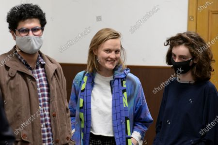 Magazine editors from left, Armen Aramyan, Natalya Tyshkevich and Alla Gutnikova wait for a court session in Moscow, Russia, . Russian authorities levied criminal charges Wednesday against four young editors of an online student magazine that had coverage about the nationwide protests supporting jailed opposition leader Alexei Navalny earlier this year