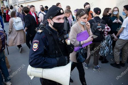 Stock Photo of Police officer patrols an area as supporter of DOXA magazine editors gather at the court building in Moscow, Russia, . Russian authorities levied criminal charges Wednesday against four young editors of an online student magazine that had coverage about the nationwide protests supporting jailed opposition leader Alexei Navalny earlier this year