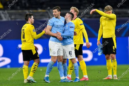 Manchester City's Phil Foden shakes hands with Dortmund's Raphael Guerreiro after the Champions League quarterfinal second leg soccer match between Borussia Dortmund and Manchester City at the Signal Iduna Park stadium in Dortmund, Germany