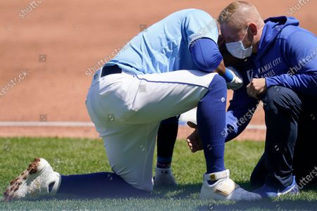 Trainer checks on Kansas City Royals' Carlos Santana after he was hit by a batted ball to end the first inning of a baseball game against the Los Angeles Angels at Kauffman Stadium in Kansas City, Mo
