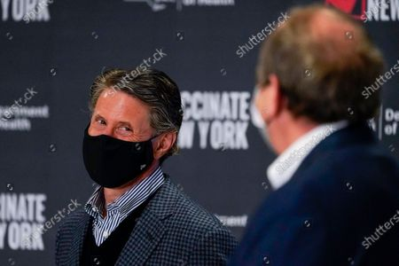 Former COO of the New York Mets Jeff Wilpon, left, looks towards Jon Ledecky, co-owner of the New York Islanders during a news conference, at a pop up COVID-19 vaccination sight at Belmont Park in Elmont, N.Y
