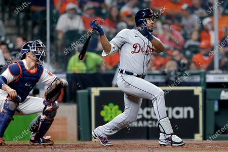 Detroit Tigers' Jeimer Candelario watches his two run RBI hit in front of Houston Astros catcher Jason Castro, left, during the fourth inning of a baseball game, in Houston