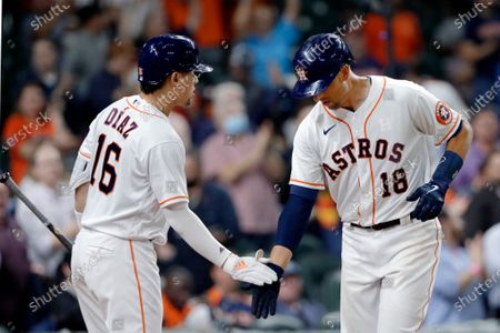 Houston Astros' Aledmys Diaz (16) and Jason Castro (18) celebrate Castro's two run home run during the fifth inning of a baseball game against the Detroit Tigers, in Houston