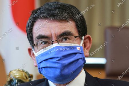 Japanese Vaccine Minister Taro Kono wearing a face mask with Japanese and EU flags on it speaks during an interview in Tokyo. Kono said, even if the Olympics go, there may be no fans of any kind in the venues. He said it's probably Olympics will have to held in empty venues, particularly as cases surge across the country