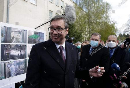 """Serbian President Aleksandar Vucic (L) and Member of the Bosnian Presidency Milorad Dodik (C) pose with vials of Sputnik V vaccine against Covid-19 during their visit at the Institute of Virology, Vaccines and Sera """"Torlak"""" in Belgrade, Serbia, 15 April 2021. Serbia has become the first country in Southern Europe to produce the Sputnik V at the """"Torlak"""" Institute, a vaccine registered in 60 countries for use against Covid-19."""