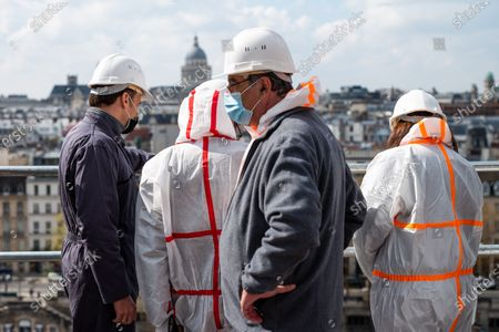 Stock Photo of French President Emmanuel Macron, architect in charge of the restoration Philippe Villeneuve (2nd R), Jean-Louis Georgelin, trained general leading the restoration efforts, Paris' Archbishop Michel Auand Paris' mayor Anne Hidalgo visit of Notre-Dame de Paris Cathedral two years since the blaze that made the spire collapse and much of the roof, in Paris on April 15, 2 2021. The actual restoration work has yet to begin as time up until now has been strengthened on securing the building, and the full restoration works should begin early next year.