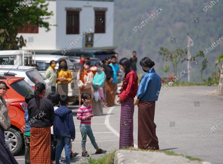 Stock Photo of Her Majesty and Ashi Yeatso speak with children in Mongar.