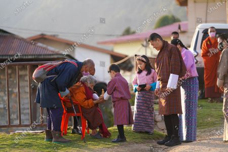 A senior citizen in Dramitreceives His Majesty's special Soelra- Sangye Ku, from His Royal Highness The Gyalsey. throughout the Royal Visit, Their Majesties continued to meet with the people of the east near their homes and places of work.