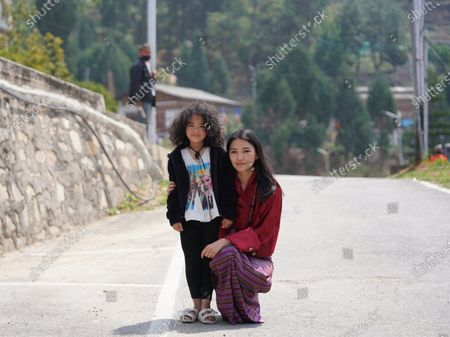 Her Majesty with a cute resident of Mongar during Their Majesties' visit.