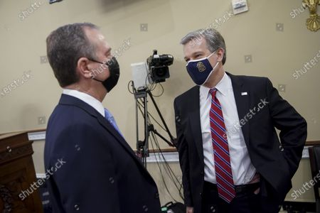 """Christopher Wray, director of the Federal Bureau of Investigation (FBI), right, wears a protective mask while talking to United States Representative Adam Schiff (Democrat of California), during a hearing in Washington, D.C., U.S.,. The hearing follows the release of an unclassified report by the intelligence community detailing the U.S. and its allies will face """"a diverse array of threats"""" in the coming year, with aggression by Russia, China and Iran."""