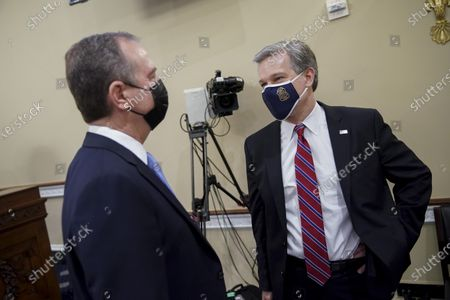 Director Christopher Wray talks with Rep. Adam Schiff, D-Calif., before a House Intelligence Committee hearing on Capitol Hill in Washington
