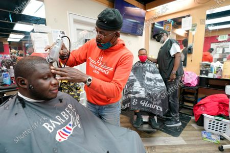 Kevin Fitzhugh, center left, cuts the hair of Mabreco Wright, left, as Wallace Wilson, right, cuts the hair of James McRae, in Hyattsville, Md. Barbers such as Fitzhugh and Wilson are members of the Health Advocates In Reach & Research (HAIR) program, which helps barbers and hair stylists to get certified to talk to community members about health. During the COVID-19 pandemic, a team of certified barbers have been providing factual information to customers about vaccines, a topic that historically has not been trusted by members of black communities because of the health abuse the race has endured over the years
