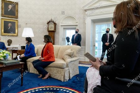 Sen. Tammy Duckworth, D-Ill., right, attends a meeting with President Joe Biden and other members of the Congressional Asian Pacific American Caucus Executive Committee in the Oval Office at the White House in Washington