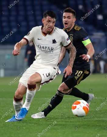 Roma's Roger Ibanez, left, and Ajax's Dusan Tadic challenge for the ball during the Europa League second leg quarterfinal soccer match between Roma and Ajax at Rome's Olympic stadium, Italy