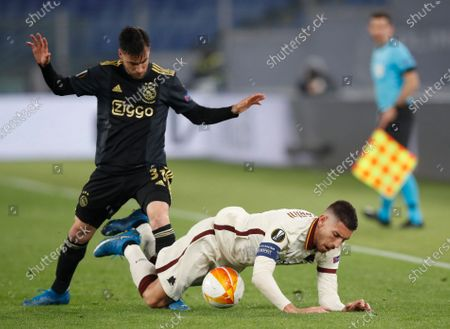 Ajax's Nicolas Tagliafico, left, and Roma's Lorenzo Pellegrini challenge for the ball during the Europa League second leg quarterfinal soccer match between Roma and Ajax at Rome's Olympic stadium, Italy