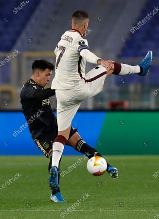 Ajax's Lisandro Martinez kicks the ball ahead of Roma's Lorenzo Pellegrini during the Europa League second leg quarterfinal soccer match between Roma and Ajax at Rome's Olympic stadium, Italy