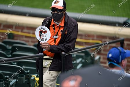 An usher reminds fans to wear their masks during a Baltimore Orioles and Seattle Mariners baseball game, in Baltimore