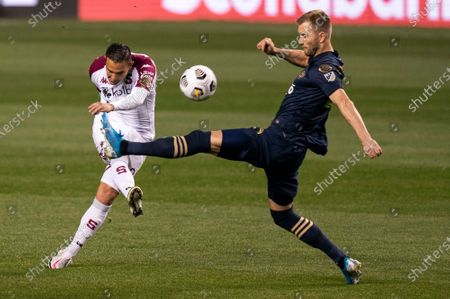 Deportivo Saprissa's David Guzman, left, kicks the ball past Philadelphia Union's Kacper Przybylko, right, during the first half of a CONCACAF Champions League soccer match, in Chester, Pa. The Union won 4-0