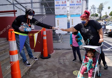 Stock Photo of Parent Melissa Ocampo is provided with a free face mask for her one-year-old, daughter Melanie, before getting her family tested at a COVID-19 testing and vaccination site run by the Los Angeles Unified School District in East Los Angeles . California Gov. Gavin Newsom is urging all schools in the state to reopen, saying there are no health barriers to getting children back into classrooms and ending distance learning