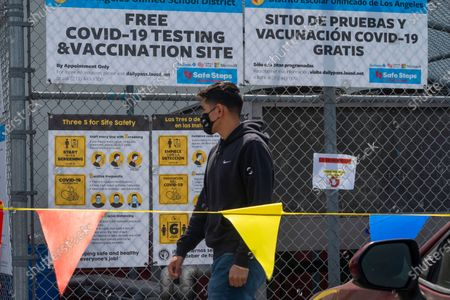 "Gustavo Cano, 21, who has already been vaccinated, reads a banner with the ""Safe Steps to Safe Schools"" instructions before getting a free test at a COVID-19 testing and vaccination site set up by the Los Angeles Unified School District in East Los Angeles . California Gov. Gavin Newsom is urging all schools in the state to reopen, saying there are no health barriers to getting children back into classrooms and ending distance learning"
