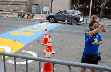 Marathoner Nikki Mansfield holds a pin that reads '4.15 Boston Day' as she poses near the finish line, in Boston, Massachusetts, USA, on 'One Boston Day', and the eighth anniversary of the bombing, 15 April 2021. On 15 April 2013, two pressure cooker bombs were detonated by the Tsarnaev brothers, Tamerlan and Dzhokhar, near the finish line, killing three spectators and injuring over 250 others. Tamerlan was later killed in a shoot out with police and Dzhokar captured and later sentenced to death following a trial, that was since vacated in July 2020 and is now awaiting a new trial. The Boston Marathon 124th running was cancelled in 2020 due to the coronavirus pandemic and the 125th is now scheduled to be held on 11 October 2021.