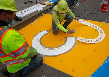 Jeff Schatz (L) and Will Belezos (R) of RoadSafe Traffic Systems, remove a stencil as they paint the Boston Marathon Finish Line on Boylston Street in Boston, Massachusetts, USA, on 'One Boston Day', and the eighth anniversary of the bombing, 15 April 2021. On 15 April 2013, two pressure cooker bombs were detonated by the Tsarnaev brothers, Tamerlan and Dzhokhar, near the finish line, killing three spectators and injuring over 250 others. Tamerlan was later killed in a shoot out with police and Dzhokar captured and later sentenced to death following a trial, that was since vacated in July 2020 and is now awaiting a new trial. The Boston Marathon 124th running was cancelled in 2020 due to the coronavirus pandemic and the 125th is now scheduled to be held on 11 October 2021.