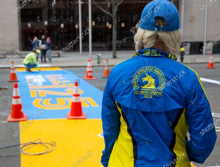 Stock Photo of Marathoner Melissa Belovich, wears a 2013 Boston Marathon jacket as she stands near the finish line as it is painted, in Boston, Massachusetts, USA, on 'One Boston Day', and the eighth anniversary of the bombing, 15 April 2021. On 15 April 2013, two pressure cooker bombs were detonated by the Tsarnaev brothers, Tamerlan and Dzhokhar, near the finish line, killing three spectators and injuring over 250 others. Tamerlan was later killed in a shoot out with police and Dzhokar captured and later sentenced to death following a trial, that was since vacated in July 2020 and is now awaiting a new trial. The Boston Marathon 124th running was cancelled in 2020 due to the coronavirus pandemic and the 125th is now scheduled to be held on 11 October 2021.