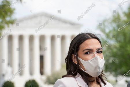 United States Representative Alexandria Ocasio-Cortez (Democrat of New York) talks to reporters following a press conference on postal banking pilot programs on the East Front of the US Capitol in Washington, DC,.
