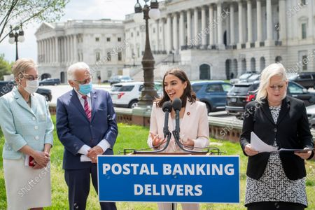 United States Representative Alexandria Ocasio-Cortez (Democrat of New York), center, is joined by United States Representative Marcy Kaptur (Democrat of Ohio), left, United States Representative Bill Pascrell (Democrat of New Jersey), second from left, and United States Senator Kirsten Gillibrand (Democrat of New York), right, as she offers remarks during a press conference on postal banking pilot programs on the East Front of the US Capitol in Washington, DC,.