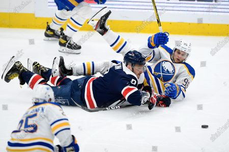 Washington Capitals left wing Alex Ovechkin (8) and Buffalo Sabres left wing Anders Bjork (96) battle for the puck during the third period of an NHL hockey game, in Washington. The Sabres won 5-2