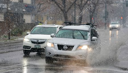 Motorist guides a sports-utility vehicle through a large large puddle in the intersection of westbound Speer Boulevard and Washington Street as a storm packing strong winds, rain and light snow sweeps over the intermountain West late, in Denver. Forecasters are predicting up to eight inches of snow in some parts of the state before the spring storm moves out on to the plains