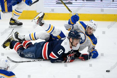 Stock Image of Washington Capitals left wing Alex Ovechkin (8) and Buffalo Sabres left wing Anders Bjork (96) vie for the puck during the third period of an NHL hockey game, in Washington. The Sabres won 5-2