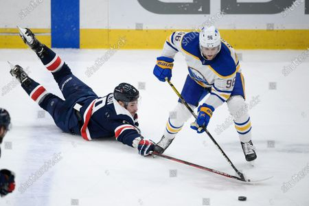 Washington Capitals defenseman Dmitry Orlov (9) reaches for the puck against Buffalo Sabres left wing Anders Bjork (96) during the third period of an NHL hockey game, in Washington. The Sabres won 5-2