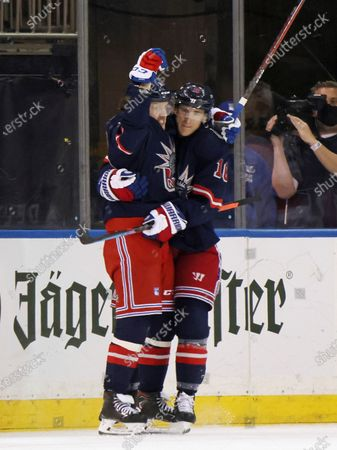 New York Rangers' Artemi Panarin, left, celebrates his goal in the first period against the New Jersey Devils and is joined by teammate Ryan Strome, right, during an NHL hockey game, in New York