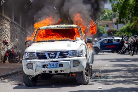 A car burns as protesters clash with police after a mass in the church of San Pedro at Petion-Ville, Port-au-Prince, Haiti, 15 April 2021. The bishops of Haiti celebrated a mass to protest against the kidnappings, after the abduction of twelve members of the clergy that occurred last weekend. Since July 2018, Haiti has been mired in a strong protest movement demanding the departure of President Jovenel Moise, whom they accuse of not keeping his promises and profiting from corruption.