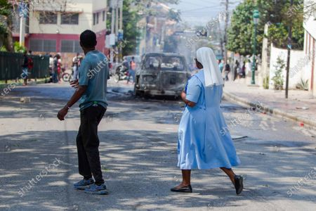 A nun (R) walks past a protest that erupted following a mass held at the church of San Pedro at Petion-Ville, Port-au-Prince, Haiti, 15 April 2021. The bishops of Haiti celebrated a mass to protest against the abduction of twelve members of the clergy on 11 April. Since July 2018, Haiti has been mired in a strong protest movement demanding the resignation of President Jovenel Moise on allegations of not keeping his promises and profiting from corruption.