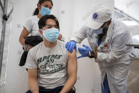 Dr. Jerry Abraham, director of Kedren Vaccines, right, gives a COVID-19 vaccination to Jose Guzman-Wug, 16, while his mom, Adriana Wug, watches at Kedren Health on Thursday, April 15, 2021 in Los Angeles, CA. Award-winning television producer, Marti Noxon, who's a big fan of Kedren Vaccines, sent an In-N-Out truck to feed 200+ volunteers who help make this vaccine program such a huge success and she did so on the day that vaccines are being made available to all people 16+ in Los Angeles. (Allen J. Schaben / Los Angeles Times)